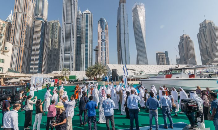 Crowd of people at Dubai International Boat Show with skyscrapers in background