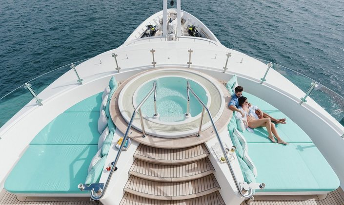 charter guests relax on sun pads that surround the Jacuzzi on the sundeck of motor yacht Ramble on Rose