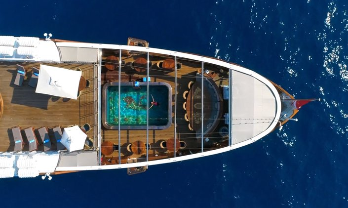 Aerial image of luxury yacht Christina O with charter guest in pool