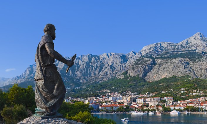 Statue of a man looking over a bay, mountains and town in Croatia