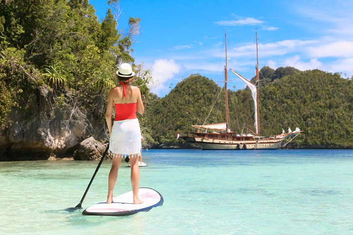 charter guest tries out the paddle board as superyacht LAMIMA anchors nearby