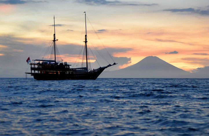 luxury yacht Dunia Baru anchors in Indonesia as the sun sets