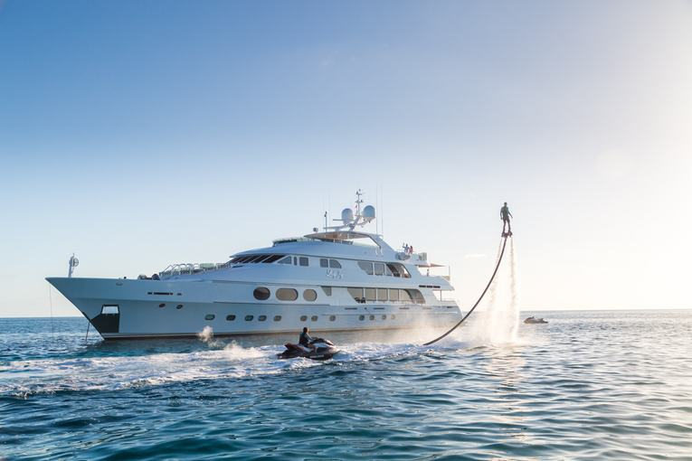 superyacht Lady Joy anchors on a Bahamas yacht charter as guests play on jet skis and Flypack