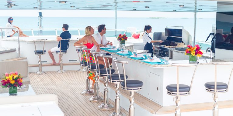 guests sit at bar and around spa pool as chef grills food on bbq on the sundeck of motor yacht Remember When